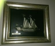 Ασημένια Ισπανική σκαλιστή Γαλέρα, με δερμάτινη μαύρη πλάτη σε ξύλινη λευκόχρυση κρακελέ προθήκη, με λευκό τζάμι και σφραγίδα γνησιότητας στην πλάτη, 1.350€